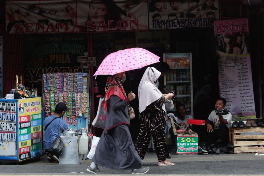 Women walk on front of a store amid the ease of Covid-19 restrictions in Bogor, Indonesia, on Oct 11, 2021.