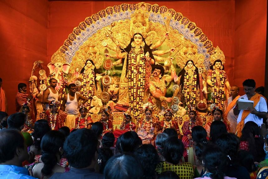 Hindu devotees stand in front of a temporary place of worship during the Durga Puja festival celebrations in Kolkata on Oct 13, 2021.