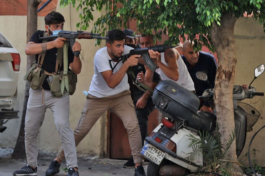 Fighters from the Shi'ite Hizbollah and Amal movements taking aim during clashes in Tayouneh, in Beirut, Lebanon, on Oct 14, 2021.