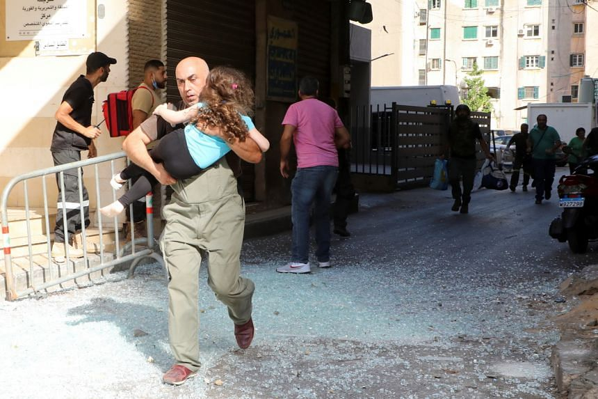 A man carrying a girl running away after gunfire erupted in Beirut on Oct 14, 2021.