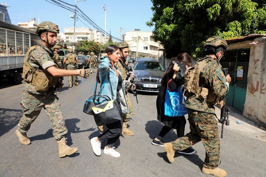 Lebanese soldiers helping civilians fleeing after gunfire erupted in Beirut on Oct 14, 2021.