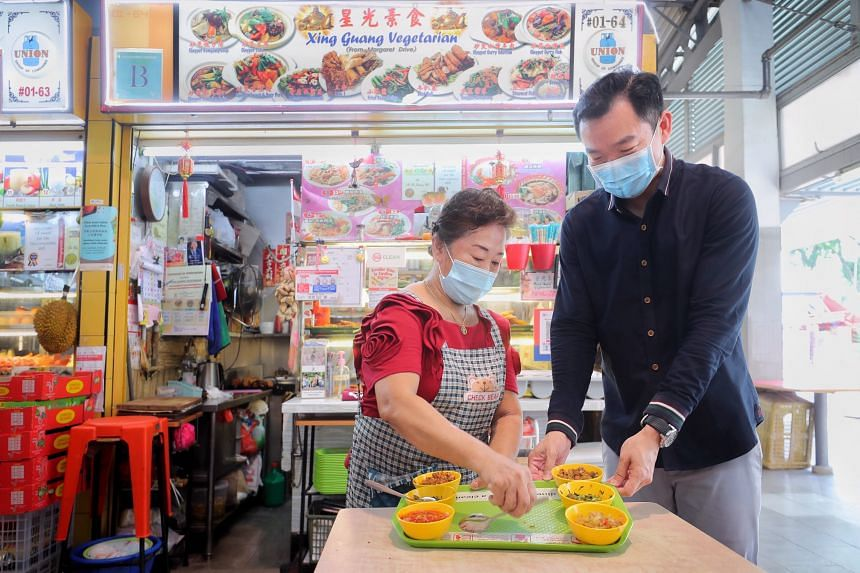 Mdm Lina Ang showing Parliamentary Secretary for MCCY and MSF Eric Chua some samples of her chopped and minced dishes available at her stall at Alexandra Village Food Centre on Oct 14, 2021.