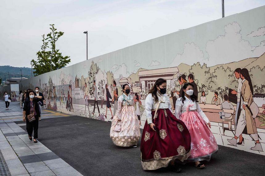 Three women wearing traditional hanbok dress walk on a pavement in Seoul.