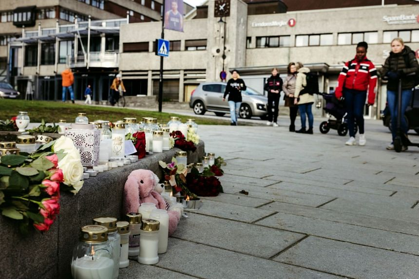 People gather at a makeshift memorial for victims of a bow-and-arrow attack a day earlier, in Kongsberg, Norway, on Oct 14, 2021.