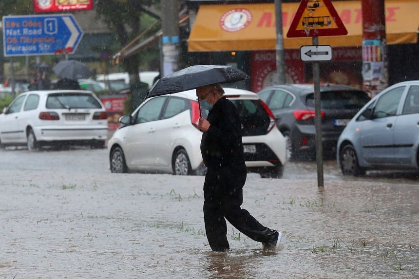 A man makes his way across a road under heavy rain in Athens, on Oct 14, 2021.