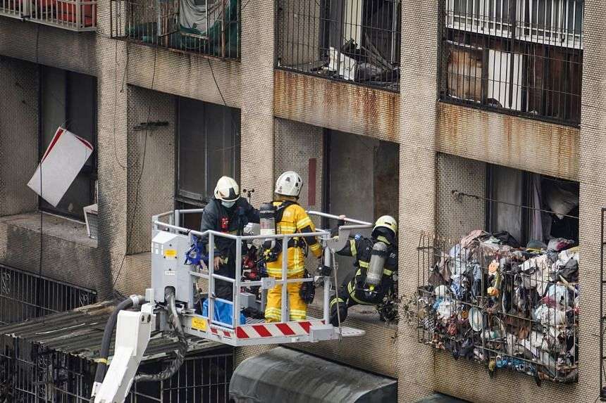 Firefighters conducting search operations after an overnight fire tore through a building in Kaohsiung, on Oct 14, 2021.