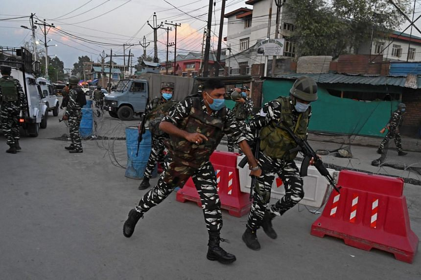 Indian security personnel rushing to the site where a man was shot dead by gunmen in downtown Srinagar earlier this month.