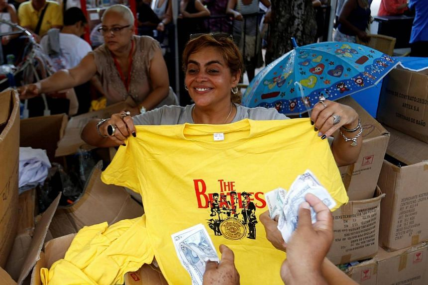 Fans buy shirts during an open-air concert in celebration of the release of the band's landmark album Sgt. Pepper's Lonely Hearts Club Band 50 years ago, in Havana, Cuba.