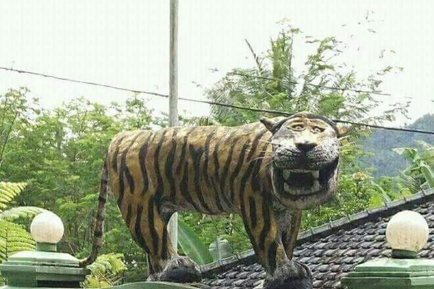 A grinning tiger statue has been removed by the Indonesian military from outside an army base after it was mocked by netizens.