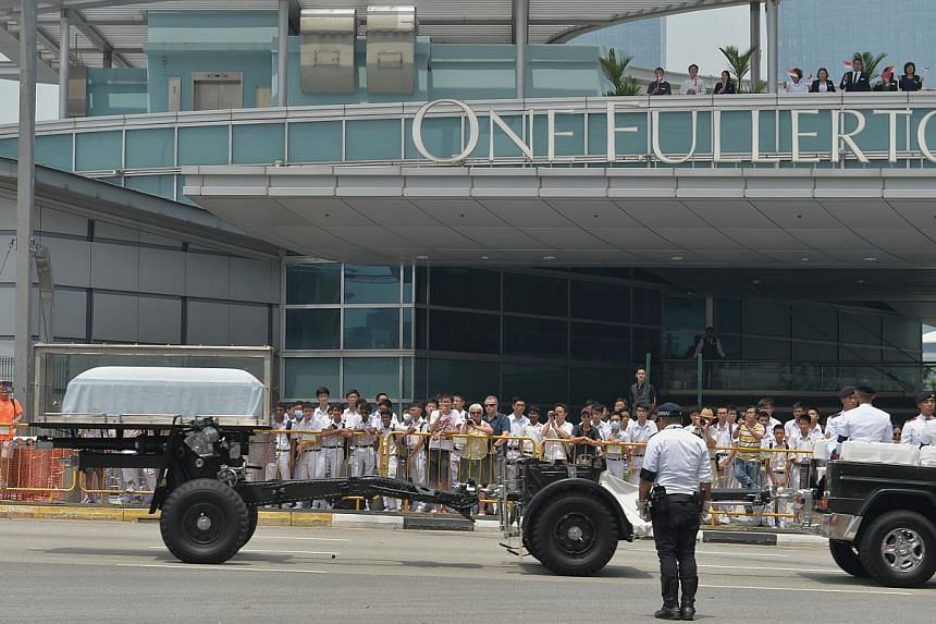 People lining up outside One Fullerton to pay their final respects as the gun carriage carrying the late former president S R Nathan goes past, on Aug 26, 2016.