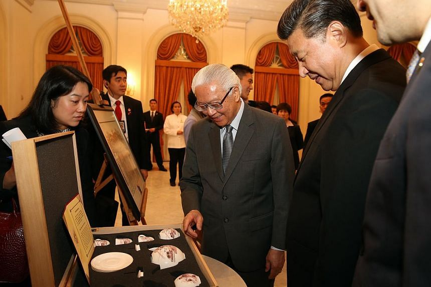 President Tony Tan admiring the bone china tea and coffee set, which has Great Wall and Merlion designs.