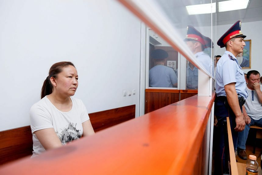 Sayragul Sauytbay sits inside a defendants' cage during a hearing at a court in the city of Zharkent.