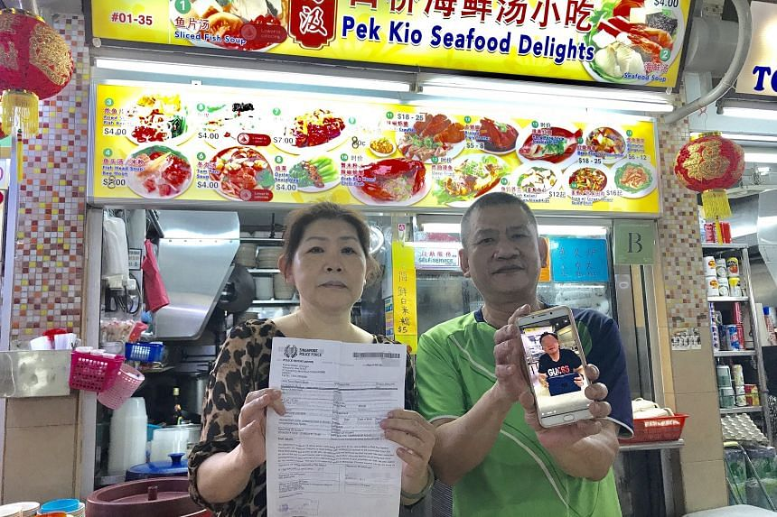 Mrs Chen and her husband hold up the police report and a photo of the man who had allegedly posed as a Shin Min food reporter and cheated her of $500.