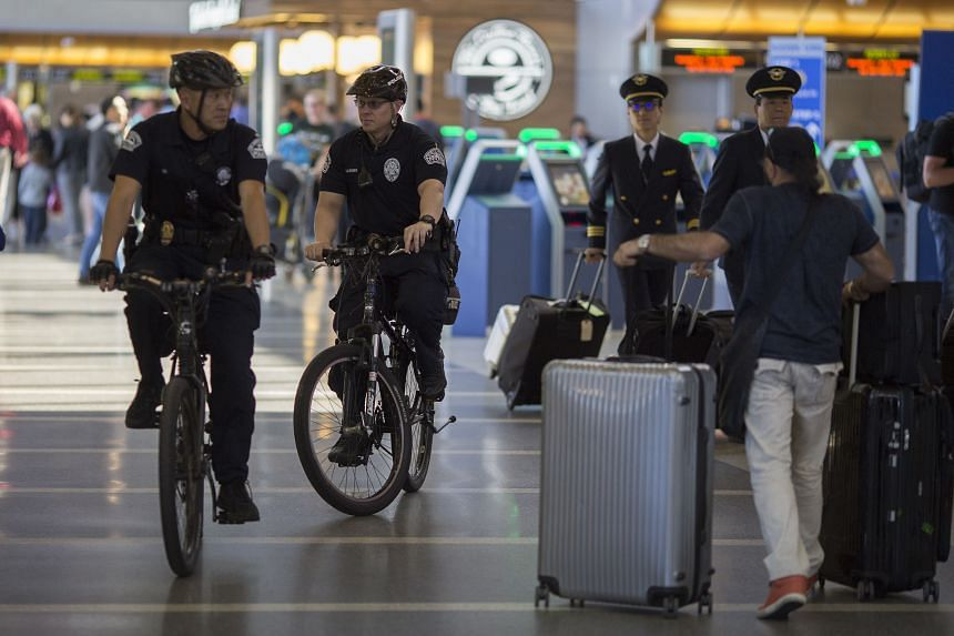 Airport police patrol on bicycle in Tom Bradley International Terminal at LAX airport.