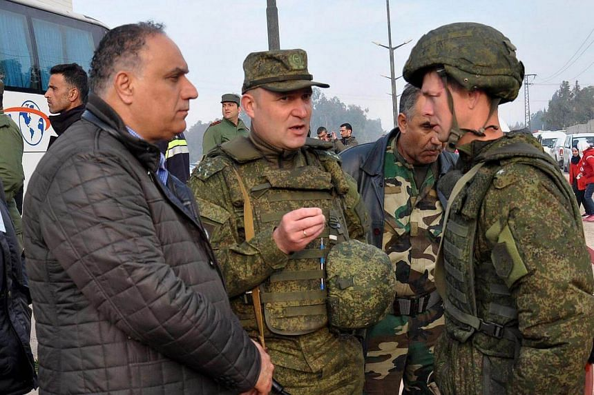The Homs governor Talal Barazi (left) with Russian army officers overseeing the preceedings during the second phase of the government-led evacuation from the rebels-held al-Waer neighborhood, in the western outskirts of the central city of Homs, Syri
