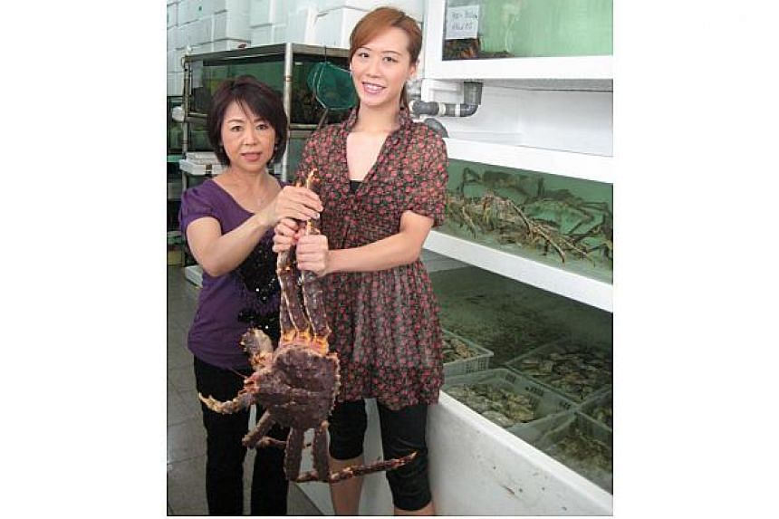 Owner Mrs Lily Loy and daughter Jenny Loy holding an Alaskan King Crab at their store, Allswell Marketing Live Seafood Market in Geylang Road in 2009.