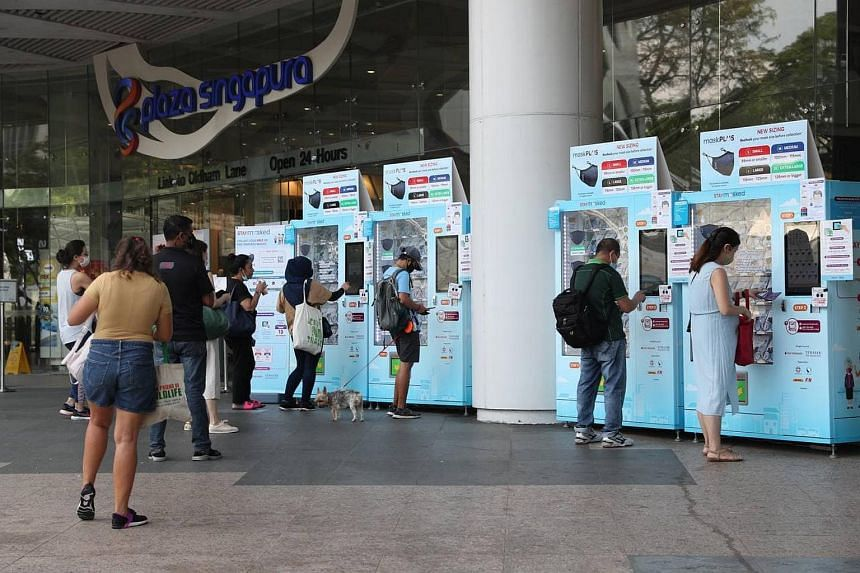 People collecting their free masks at vending machines outside Plaza Singapura, on March 1, 2021.