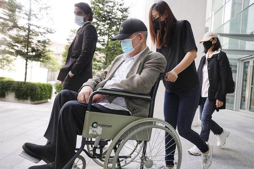 O.K. Lim (in wheelchair) arriving in court on Friday morning with his lawyer Mr Navin Thevar (left).
