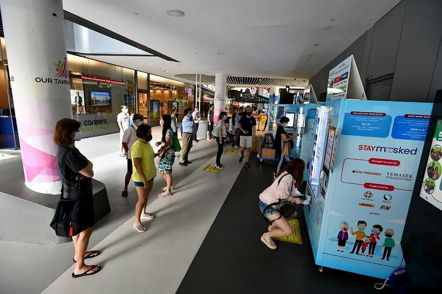 People collecting their free masks at the mask vending machines at Our Tampines Hub, on March 1, 2021.