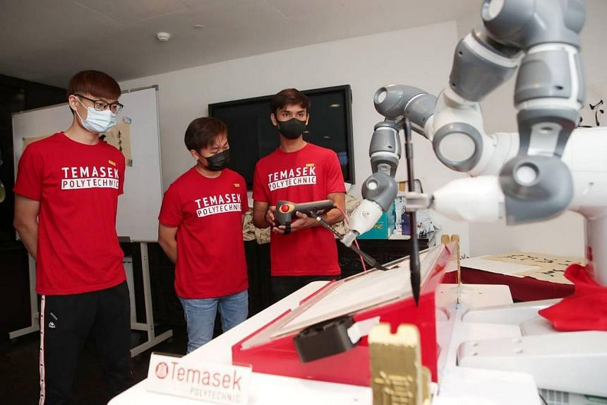(From left) Students Xavier Teng, Nicholas Yeo and Elfiqri Ashriq at the preview of a YuMi robot performing Chinese calligraphy, on April 21, 2021.
