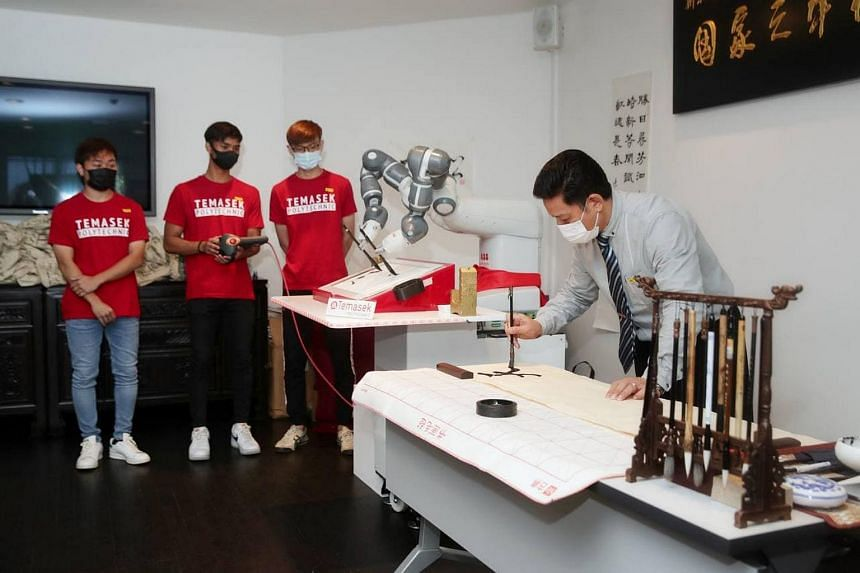 (From left) Students Nicholas Yeo, Elfiqri Ashriq, and Xavier Teng, showcasing a YuMi robot performing Chinese calligraphy together with Mr Ma Shuang Lu, on April 21, 2021.