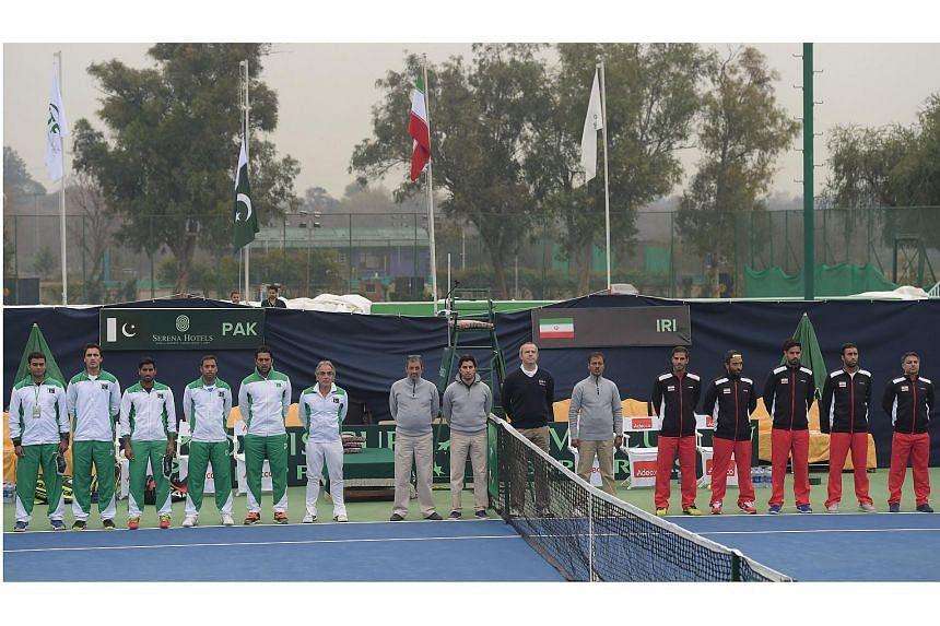 The Davis Cup teams of Pakistan (left) and Iran standing for their countries' national anthems, in Islamabad on Feb 3, 2017.