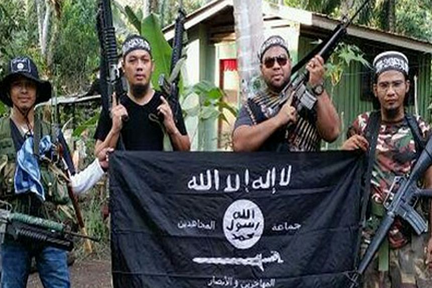 An Abu Sayyaf fighter (left) poses with Malaysian militants and Islamic State in Iraq and Syria (ISIS) flag in 2015.