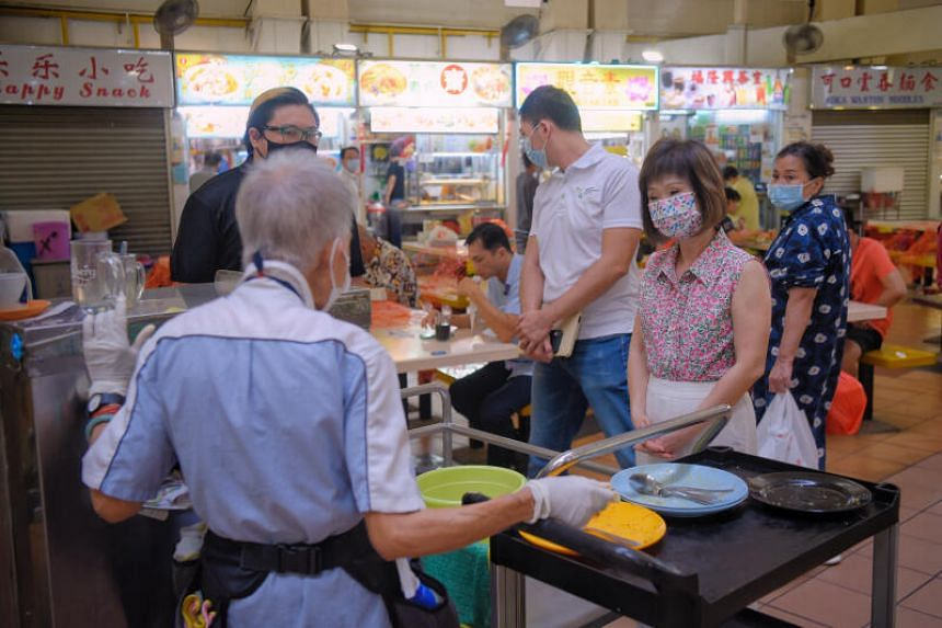 Dr Amy Khor (far right) speaking to a cleaner at North Bridge Road Market and Food Centre on June 22, 2021.
