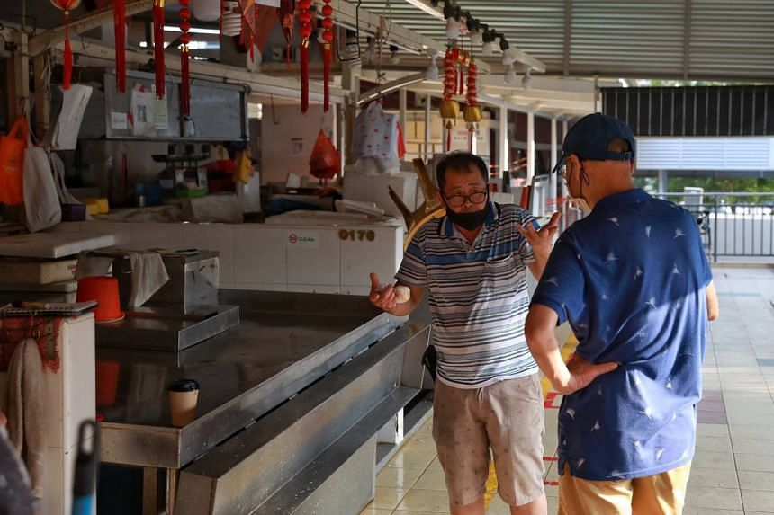 A fishmonger gesturing to a customer that there is no sale of fish at Kovan 209 Market and Food Centre on July 18, 2021.