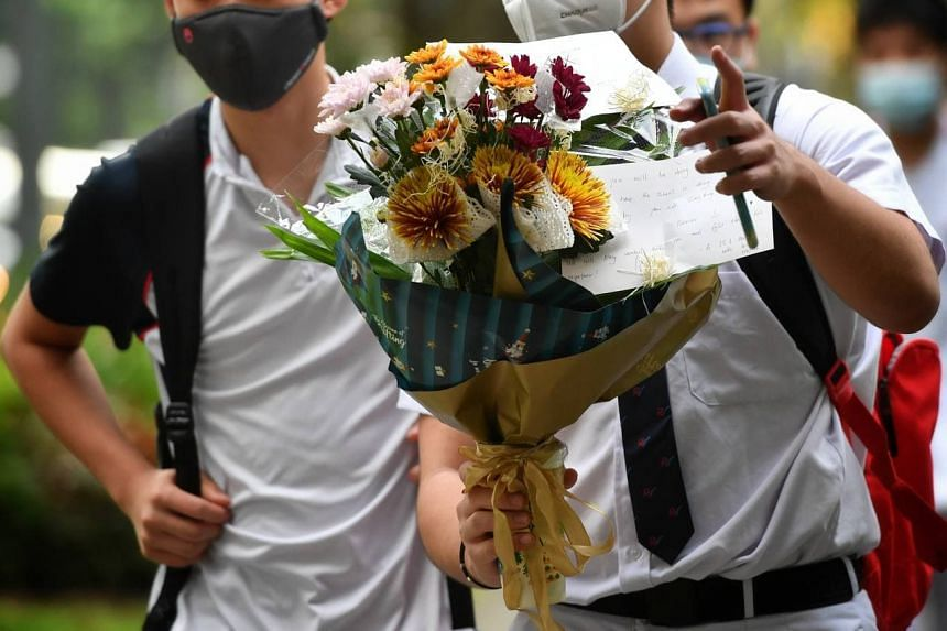 Students bring flowers to pay their respects to their schoolmate at River Valley High School on July 21, 2021.