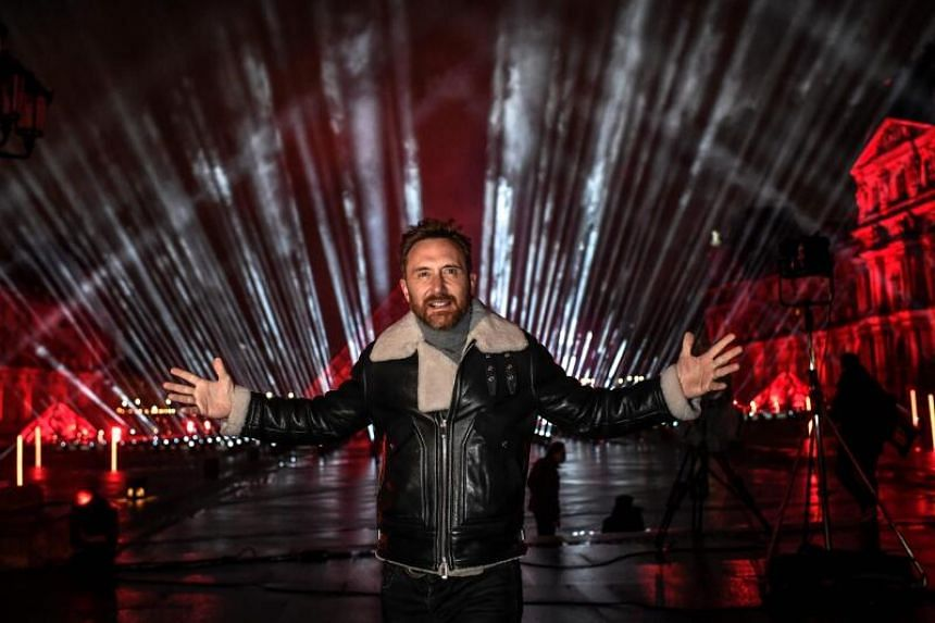 """French DJ David Guetta on the stage set up for his 2021 New Year's eve livestream charity concert """"United at Home"""" in front of the Louvre Pyramid on Dec 29, 2020."""