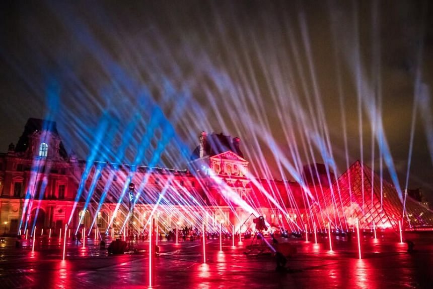 Lights are projected on the Louvre's Museum Pyramid during the tuning of the performance on Dec 29, 2020.