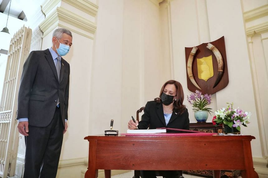 Prime Minister Lee Hsien Loong looks on as US Vice-President Kamala Harris signs the guestbook at the Istana on Aug 23, 2021.