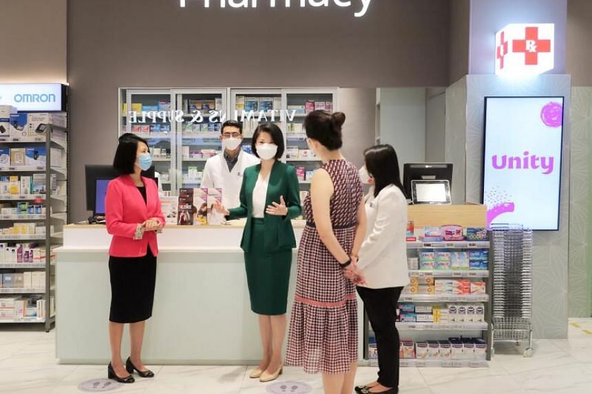 Ms Sun Xueling at the Unity Pharmacy store at VivoCity speaking to pharmacists who had undergone the training to detect signs of family violence.