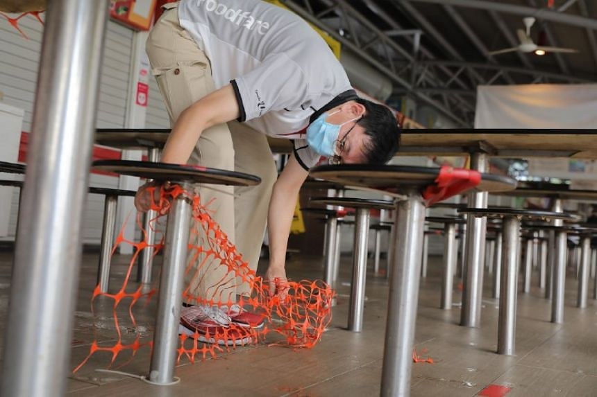 Safe distancing markers being adjusted at Toa Payoh Lorong 5 Food Centre on the first day of phase three reopening on Dec 28, 2020.
