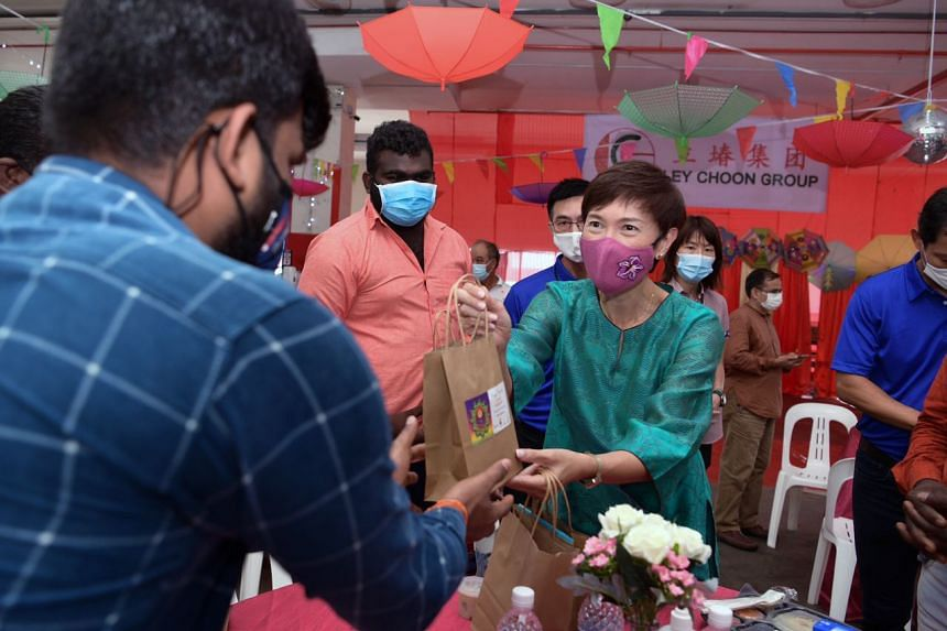 Minister for Manpower Josephine Teo giving out festive goodies to migrant workers at a factory-converted dormitory at Sungei Kadut on Nov 14, 2020.