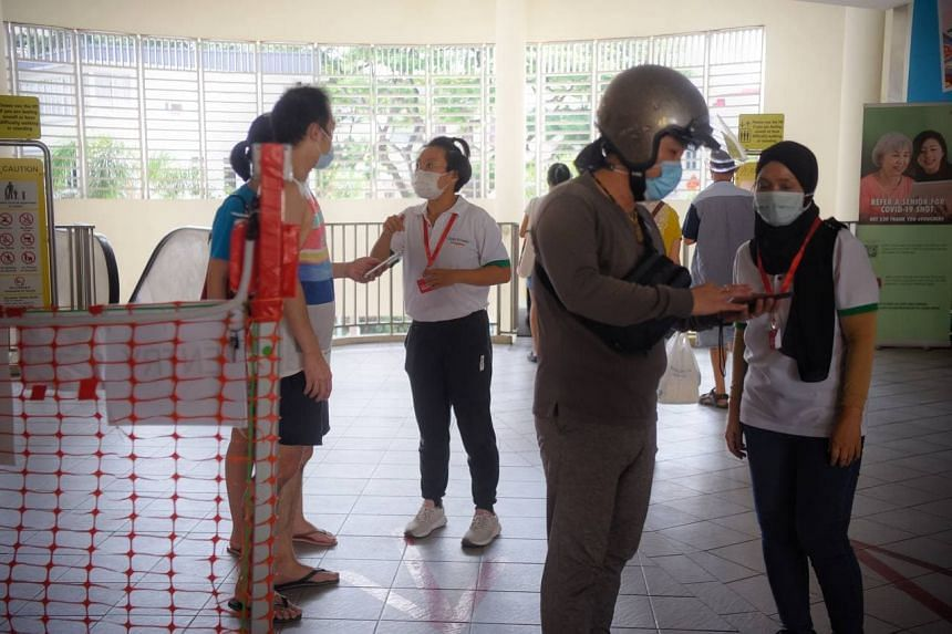 A safe distancing ambassador (left, in white) advises a man and a woman to take away their food at Tiong Bahru market on Oct 13, 2021.