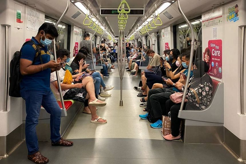 Passengers onboard a Downtown Line train heading to the city on the morning of the first day of tighter restrictions on Sept 27, 2021.