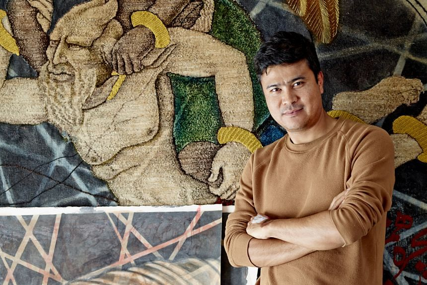 Artist Khadim Ali with a detail of the rug he has created for his show here, and his painting Transition/Evacuation 5, which shows five nude women being burnt alive by dark demons. -- PHOTO: ARNDT