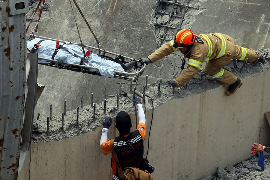 Firefighters pulling up the body of a worker at Hanwha Chemical plant, in the south-eastern city of Ulsan, yesterday. A waste-water storage tank exploded when workers were doing welding work.