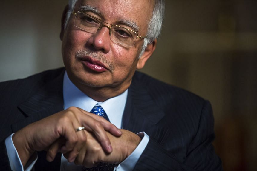 """The options may be dwindling for Mr Najib (left). The WSJ report alleged that documents from a """"government probe"""" into 1MDB (right) showed five deposits into accounts in Mr Najib's name at a Malaysian bank. Top right, the Tun Razak Exchange, a mega p"""
