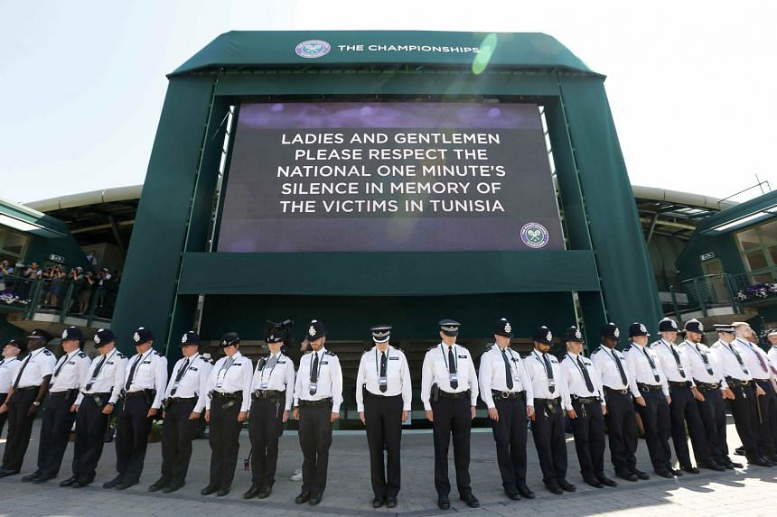 Police officers observing a national minute of silence for victims of the attacks in Tunisia a week ago at the Wimbledon Tennis Championships in London yesterday. SEE WORLD A42