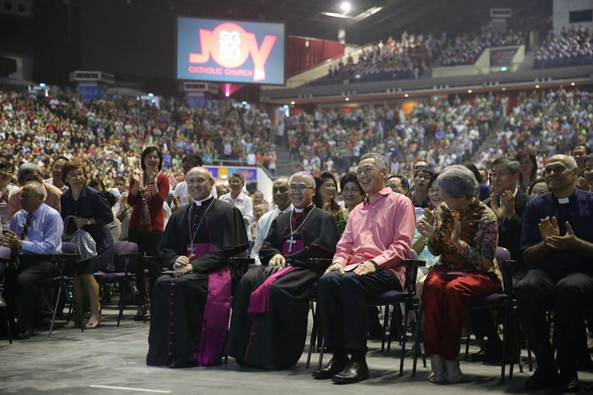 Prime Minister Lee Hsien Loong, flanked by his wife Ho Ching and Archbishop William Goh, led the tribute to Catholic pioneers who served the people and the country. ST PHOTO: ONG WEE JIN