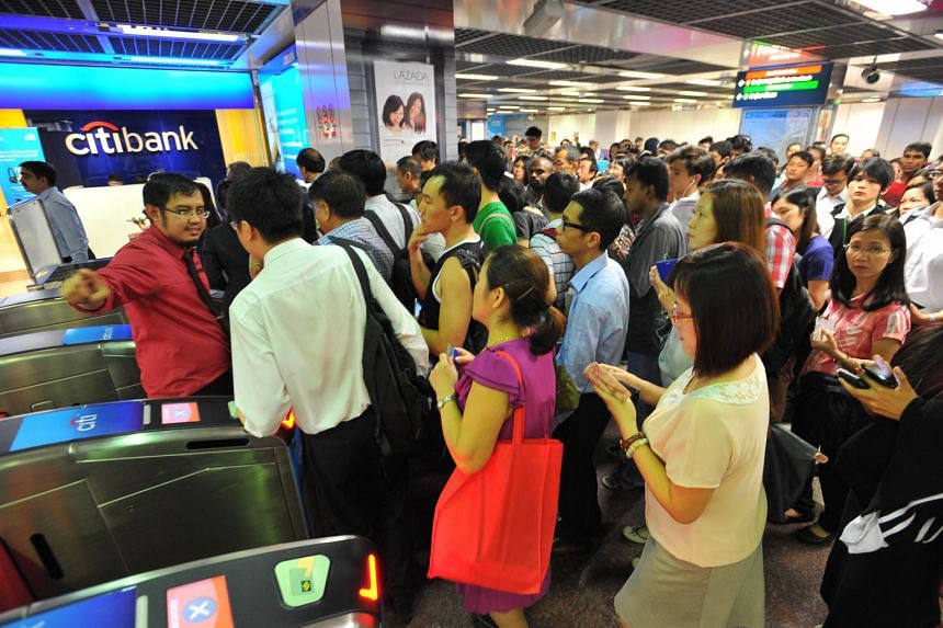 Crowds at City Hall MRT station being directed away from the fare gates leading to the trains. A power trip, which could have been caused by a faulty train, crippled services throughout the North-South and East-West lines for more than two hours from