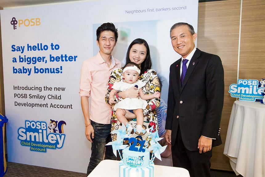 Mr Keith Tham (far left), with his wife, Ms Daphne Lian, their daughter Chloe, and Mr Jeremy Soo (left), managing director of DBS' consumer banking group, says he will switch his daughter's Child Development Account to POSB.