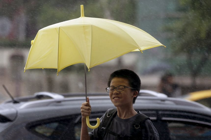 People shielding themselves from strong winds and rain brought by Typhoon Chan-hom in Taipei yesterday. Four people were injured as heavy rainfall and fierce winds battered Taiwan, with the stock market, schools and offices shut. More than 1,000 vill