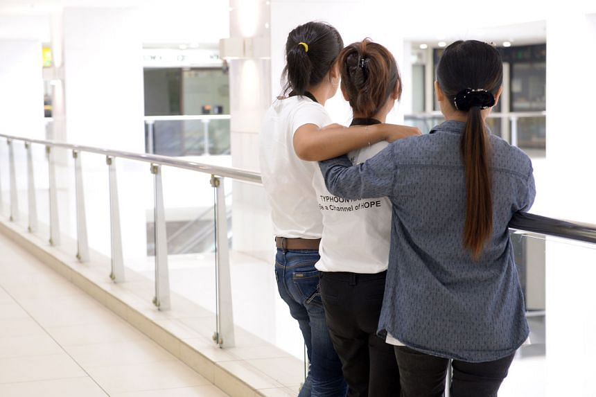 Myanmar maid Lay Mon (right) with two other foreign domestic workers who are at Home's shelter. She wanted to return home  after three months but said her employers owed her two months' salary and would not let her end her two-year contract. They als