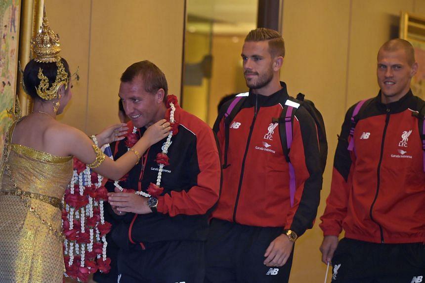 Liverpool manager Brendan Rodgers being garlanded upon arrival at Suvarnabhumi International Airport as Jordan Henderson and Martin Skrtel await their turn.