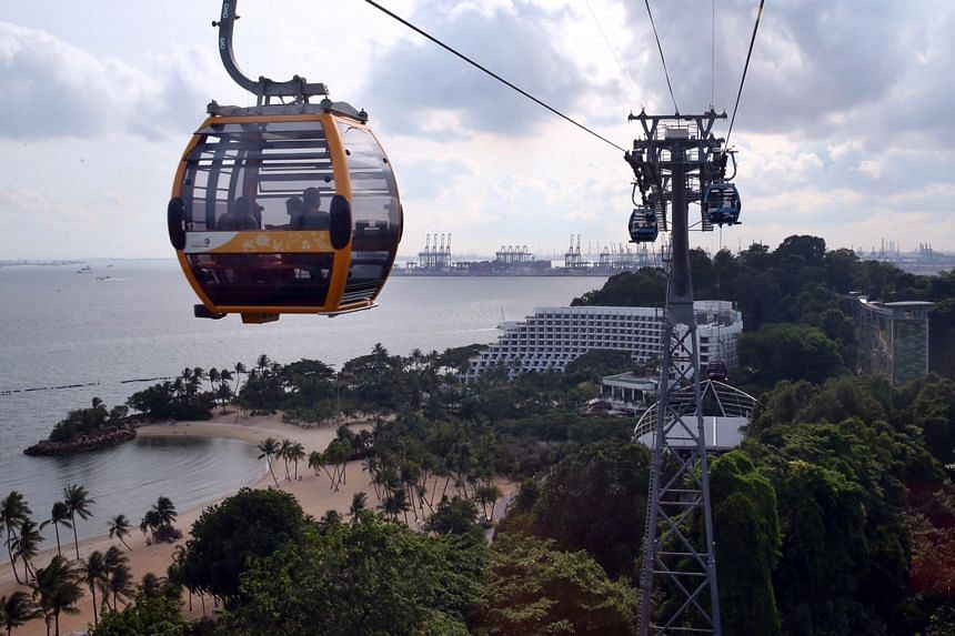 Passengers get a view of Sentosa from up high in one of the 51 cable-car cabins on the new Sentosa Line. The new intra-island travel option, costing over $78 million, was officially launched yesterday. The 890m-long link transports visitors on the is
