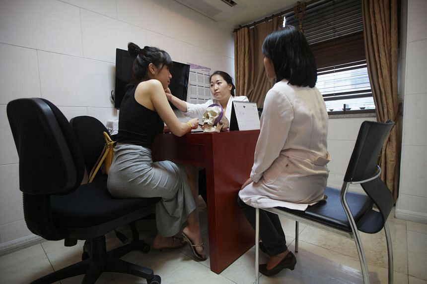 A patient (far left) meeting a counsellor (centre) and a translator at BK Plastic Surgery in Seoul. South Korea's Ministry of Health said 79,481 medical tourists arrived from China last year, and plastic surgery was the most sought-after service. Bas